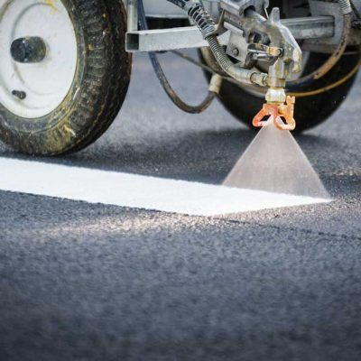 Striping machine painting white striping line on asphalt road - Southern Striping, LLC